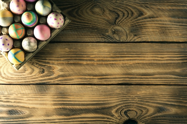 Uova di pasqua su un supporto su una superficie di legno con posto per il testo, vista dall'alto