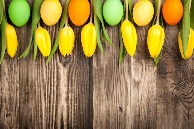 Uova di pasqua e tulipani su fondo di legno