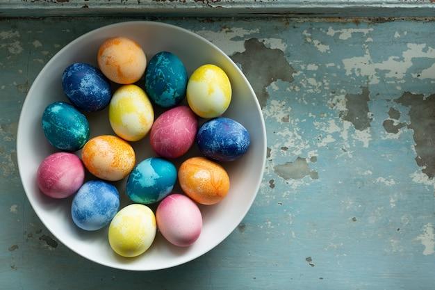 Uova di pasqua nel piatto bianco su vecchio fondo di cemento azzurro
