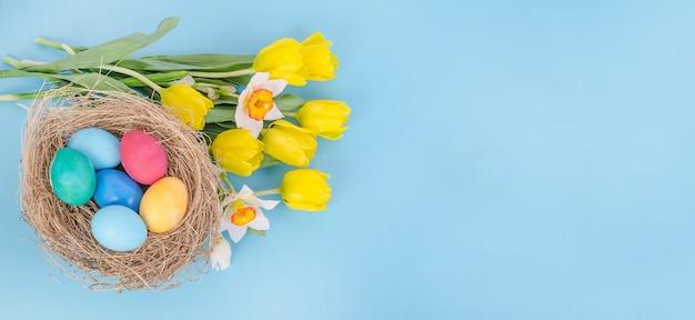 Uova di pasqua con un bouquet di tulipani gialli e narcisi su sfondo blu, con spazio di copia
