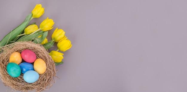 Uova di pasqua con un mazzo di tulipani gialli su sfondo grigio, con spazio di copia