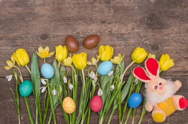 Uova di pasqua con un mazzo di tulipani gialli e un coniglio su uno sfondo di legno, con spazio di copia
