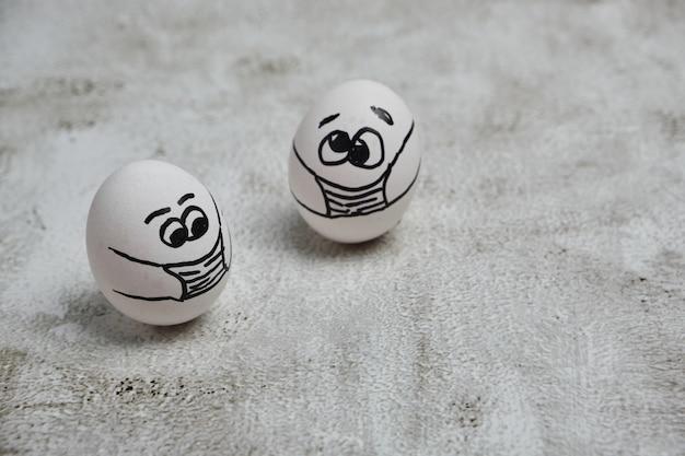 Uova di pasqua con concetti di protezione covid 19. uova di pasqua fai-da-te con facce buffe dipinte che indossano una maschera per la decorazione delle vacanze di pasqua. messa a fuoco selettiva con copia spazio.