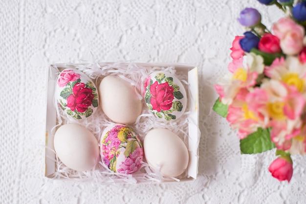 Uova di pasqua con un motivo floreale su uno sfondo bianco con fiori. spazio per il testo