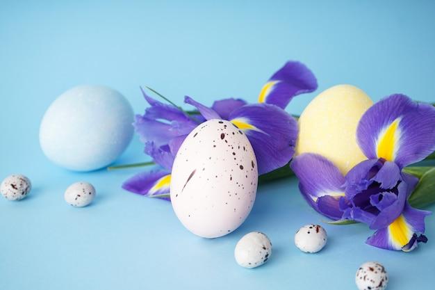 Uova di pasqua con fiori su una superficie blu. avvicinamento.