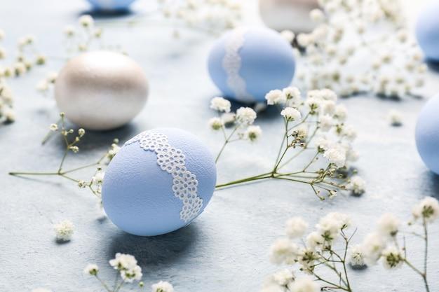 Uova di pasqua con fiori su sfondo colorato