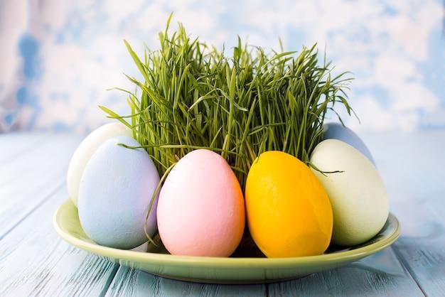 Uova di pasqua con erba servite sul piatto su una superficie blu