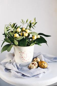 Uova di pasqua con rami verdi e bacche gialle su sfondo bianco e grigio. buone vacanze di pasqua, vista frontale.
