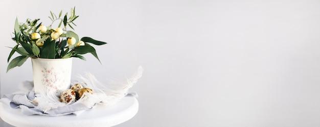 Uova di pasqua con rami verdi e bacche gialle su sfondo bianco e grigio con spazio per il testo. ampia composizione. buone vacanze di pasqua, vista frontale.