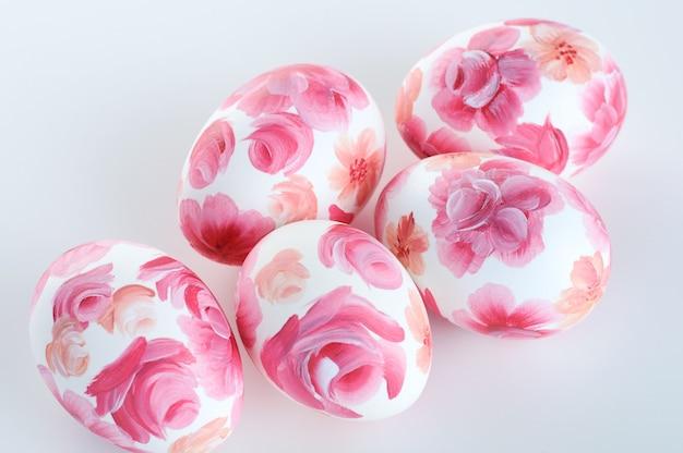 Uova di pasqua con stampa floreale rosa su sfondo bianco, copia spazio, happy easte