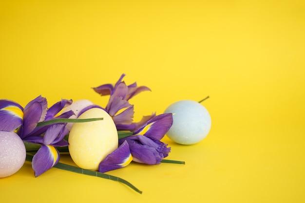 Uova di pasqua con fiori viola su sfondo giallo