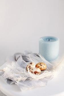 Uova di pasqua con piuma bianca su sfondo bianco e grigio. copia spazio. buone vacanze di pasqua, vista frontale e dall'alto.