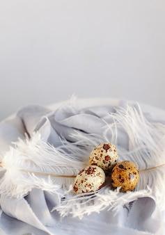 Uova di pasqua con piuma bianca su sfondo bianco e grigio. buone vacanze di pasqua, vista frontale e dall'alto.