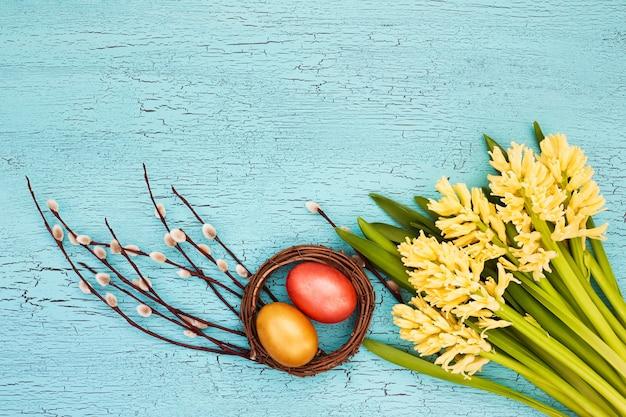 Uova di pasqua e fiori primaverili gialli su sfondo blu