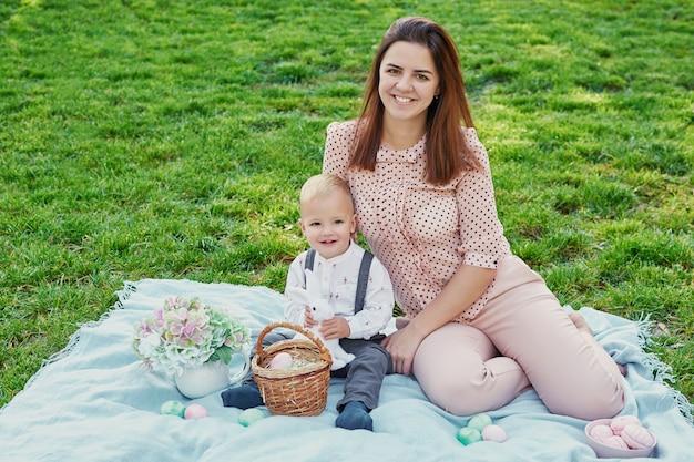 Picnic in famiglia di pasqua, raccolta delle uova, famiglia allegra in vacanza nel parco. concetto di vacanze di primavera.