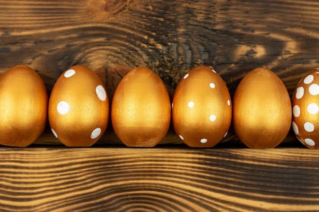 Priorità bassa festiva di pasqua. vista dall'alto di uova di pasqua colorate con vernice dorata su sfondo di legno scuro.