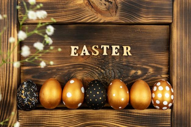 Priorità bassa festiva di pasqua. vista dall'alto di uova di pasqua colorate con vernice dorata e iscrizione in inglese pasqua. lettere in legno su fondo di legno scuro.
