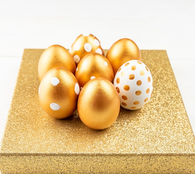 Decorazione festiva di pasqua primo piano delle uova di pasqua colorate con vernice dorata sul podio scintillante. vari disegni punteggiati.
