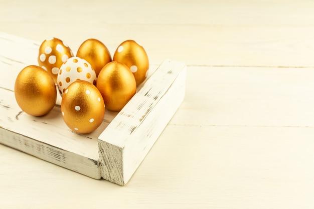 Decorazione festiva di pasqua. primo piano di uova di pasqua colorate con vernice dorata sul vassoio in legno bianco. vari disegni punteggiati.