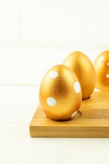 Decorazione festiva di pasqua primo piano delle uova di pasqua colorate con vernice dorata sul podio di legno. vari disegni punteggiati.