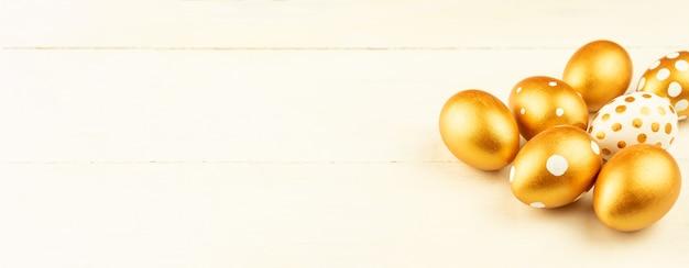 Decorazione festiva di pasqua primo piano delle uova di pasqua colorate con vernice dorata su una superficie di legno. vari disegni punteggiati. banner