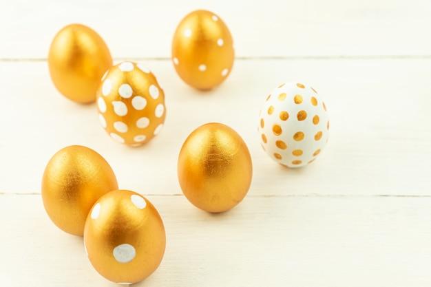 Decorazione festiva di pasqua primo piano delle uova di pasqua colorate con vernice dorata su una superficie di legno. vari disegni punteggiati.