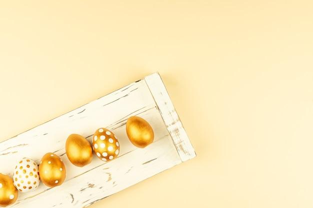 Decorazione festiva di pasqua. vista dall'alto di uova di pasqua colorate con vernice dorata e cornice vuota mock-up. vari disegni punteggiati. sfondo bianco.