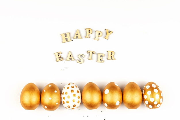 Decorazione festiva di pasqua. vista dall'alto di uova di pasqua colorate con vernice dorata e scritta in inglese buona pasqua. lettere in legno su sfondo bianco. vari design punteggiato.