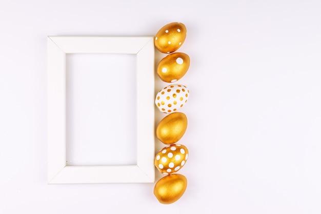 Decorazione festiva di pasqua. vista dall'alto di uova di pasqua colorate con vernice dorata vari disegni punteggiati. superficie bianca.
