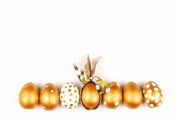 Decorazione festiva di pasqua vista dall'alto delle uova di pasqua colorate con vernice dorata sulla superficie bianca. vari disegni punteggiati.