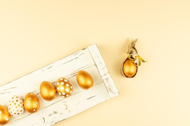 Decorazione festiva di pasqua. vista dall'alto di uova di pasqua colorate con vernice dorata sul vassoio in legno bianco. vari disegni punteggiati.