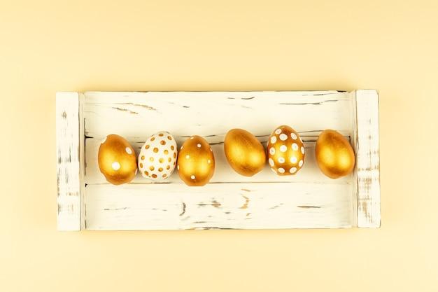 Decorazione festiva di pasqua. vista dall'alto di uova di pasqua colorate con vernice dorata.