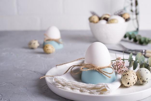 Regolazione festiva della tavola di pasqua con le uova bianche del pollo in portauova, rametti di foglia di eucalipto. .