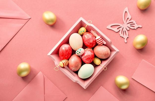 Piatto di pasqua disteso su carta color corallo con vassoio in legno pieno di uova decorative, biglietti di auguri, buste e fiori decorativi