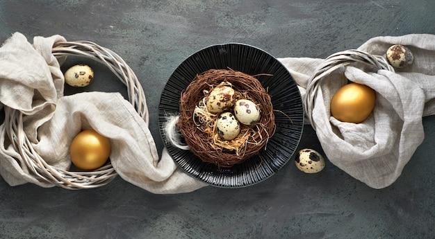 Il piatto pasquale giaceva su sfondo scuro con uova di quaglia nel nido, lino fabrique e due uova d'oro su oscurità