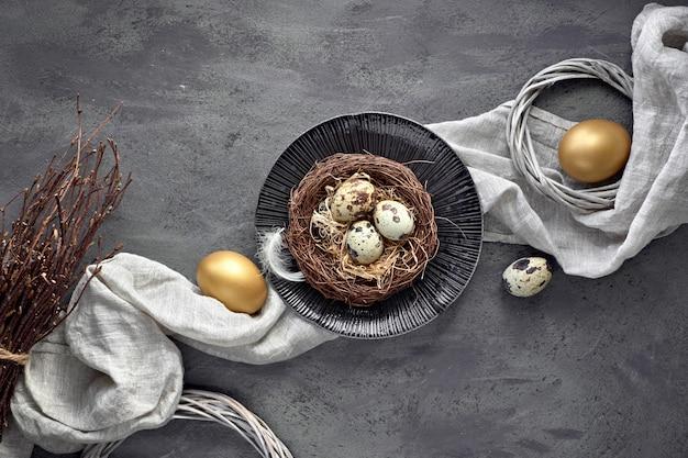 Il piatto pasquale giaceva sul muro scuro con uova di quaglia nel nido, tessuto di lino e due uova dorate sul buio