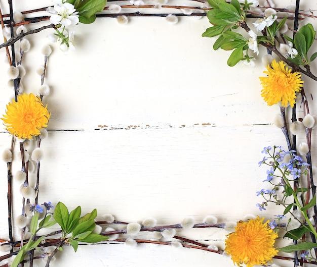 Nido di sfondo cornice di pasqua con i denti di leone dipinti di fiori di salice uovo su una vista superiore del fondo di legno bianco Foto Premium