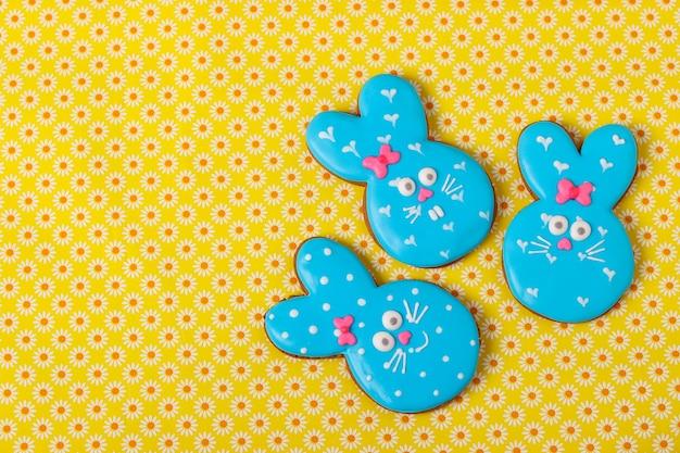 Conigli divertenti di pasqua, biscotti di panpepato dipinti in casa in smalto su sfondo giallo, vista dall'alto