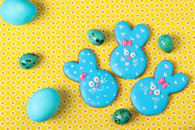 Conigli divertenti di pasqua, biscotti di pan di zenzero dipinti in casa in smalto su una superficie gialla, vista dall'alto