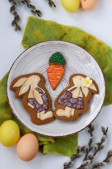 I coniglietti di pan di zenzero pasquale si trovano in un piatto su sfondo bianco, vista dall'alto, il concetto della festa di primavera in chiesa