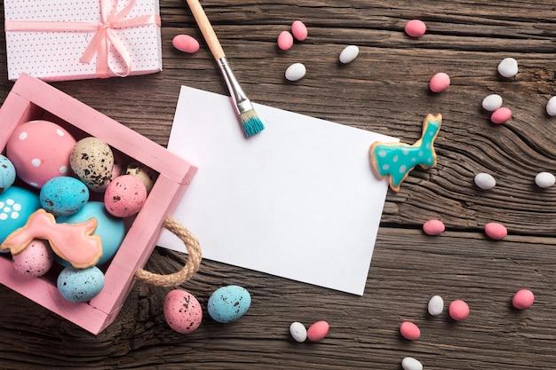 Biscotti di panpepato di pasqua sulla tavola di legno. conigli e uova. biglietto d'auguri. vista dall'alto con spazio per i tuoi saluti.