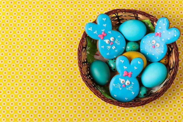 Conigli di panpepato pasquale, pollo giallo e blu e uova di quaglia in un cesto di vimini, concetto di vacanza di primavera, vista dall'alto