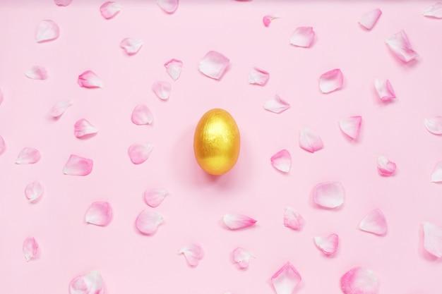 Decorazione uovo di pasqua in oro e petali di rosa dai colori tenui.