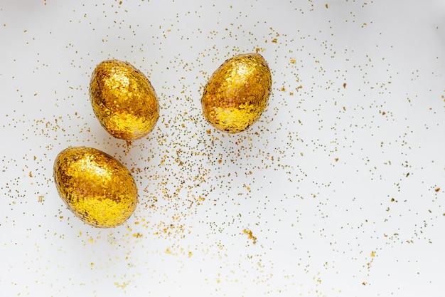 Uova decorate dorate di pasqua in nido su fondo bianco. spazio minimo della copia di concetto di pasqua per testo.