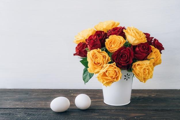 Biglietto di auguri di pasqua. uova e un bellissimo bouquet di rose gialle e rosse in bianco