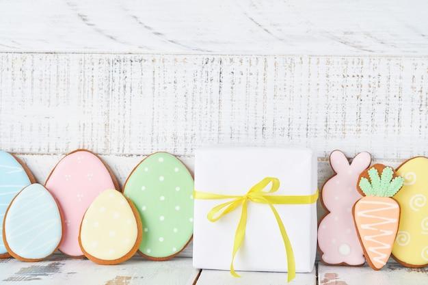 Cartolina d'auguri di pasqua con conigli colorati, uova, polli e biscotti di panpepato di carote su fondo di legno bianco vecchio con spazio di copia. modello. bandiera. vista dall'alto.