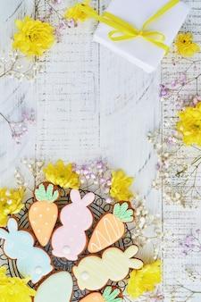 Biglietto di auguri di pasqua con conigli colorati, uova, polli e biscotti di panpepato di carote su fondo di legno bianco vecchio con lo spazio della copia. vista dall'alto.