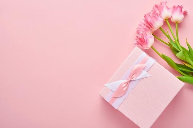 Biglietto di auguri di pasqua con scatola regalo di uova di panpepato pasquale e fiori di tulipano su sfondo rosa