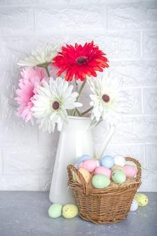 Concetto di auguri di pasqua. priorità bassa festiva di pasqua con i fiori di primavera, uova colorate dipinte in un cestino.