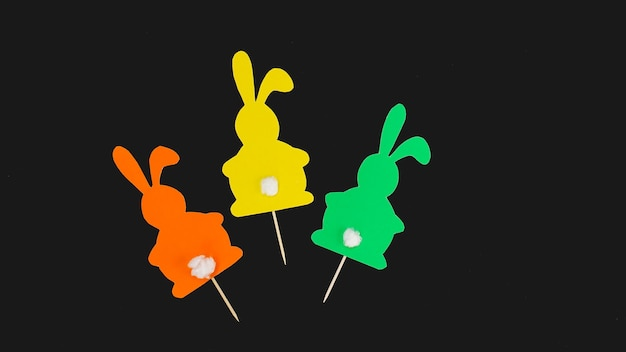Pasqua fatta a mano. decorazioni fatte a mano per le vacanze. i conigli di carta colorata sono attaccati agli stuzzicadenti. può essere usato per decorare i cupcakes di pasqua
